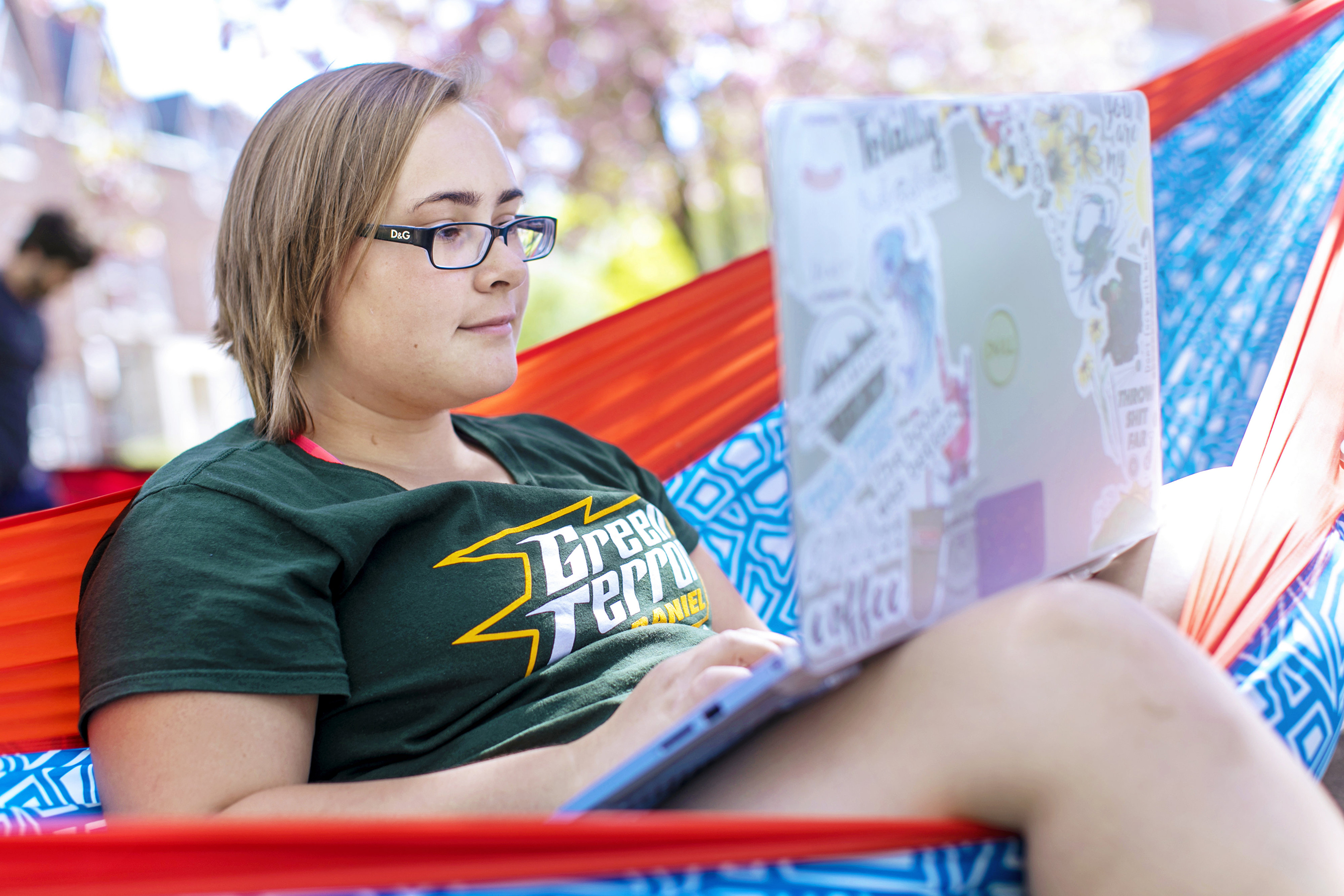 Student on computer in hammock on campus.