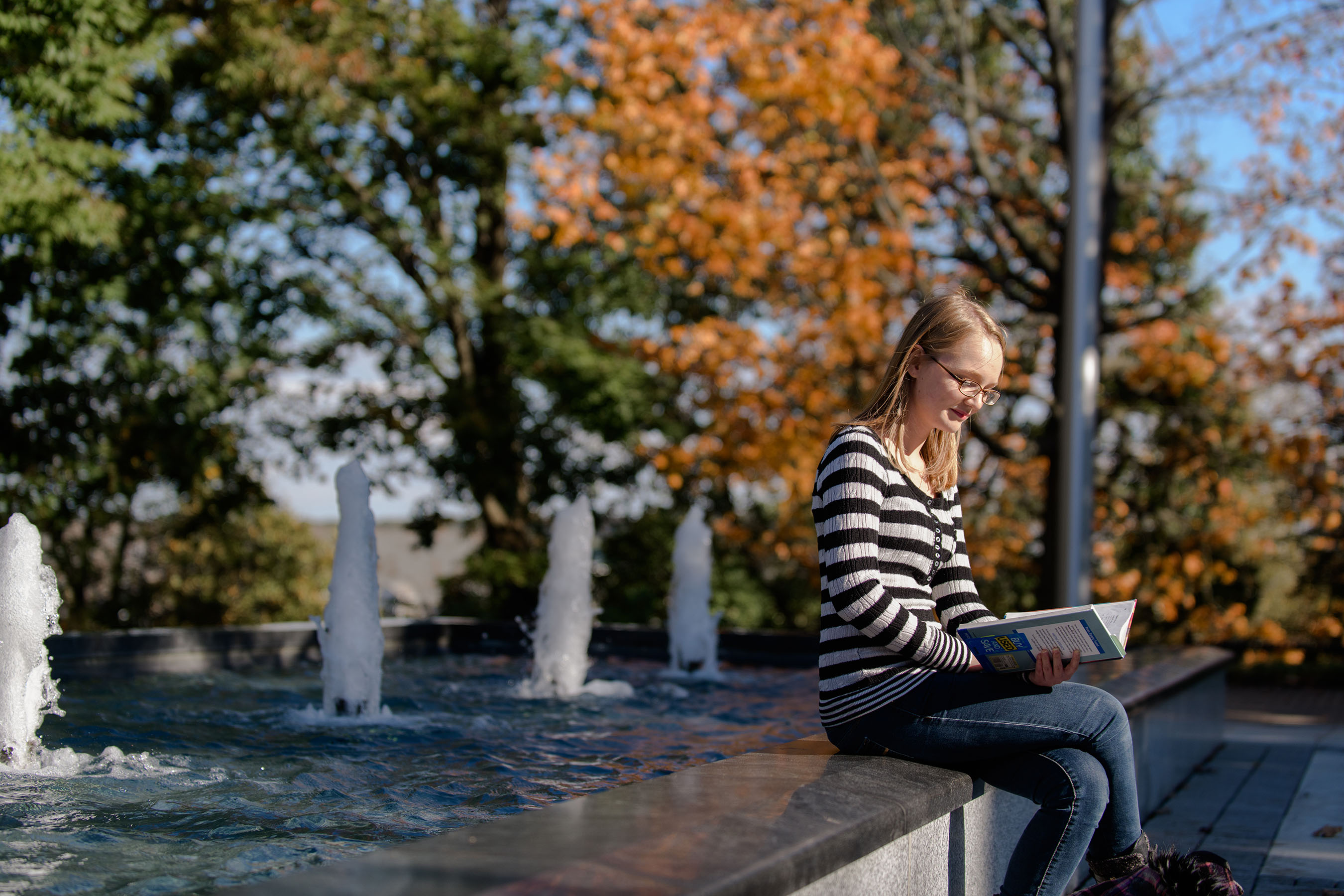 Student reading book sitting on fountain edge on campus.