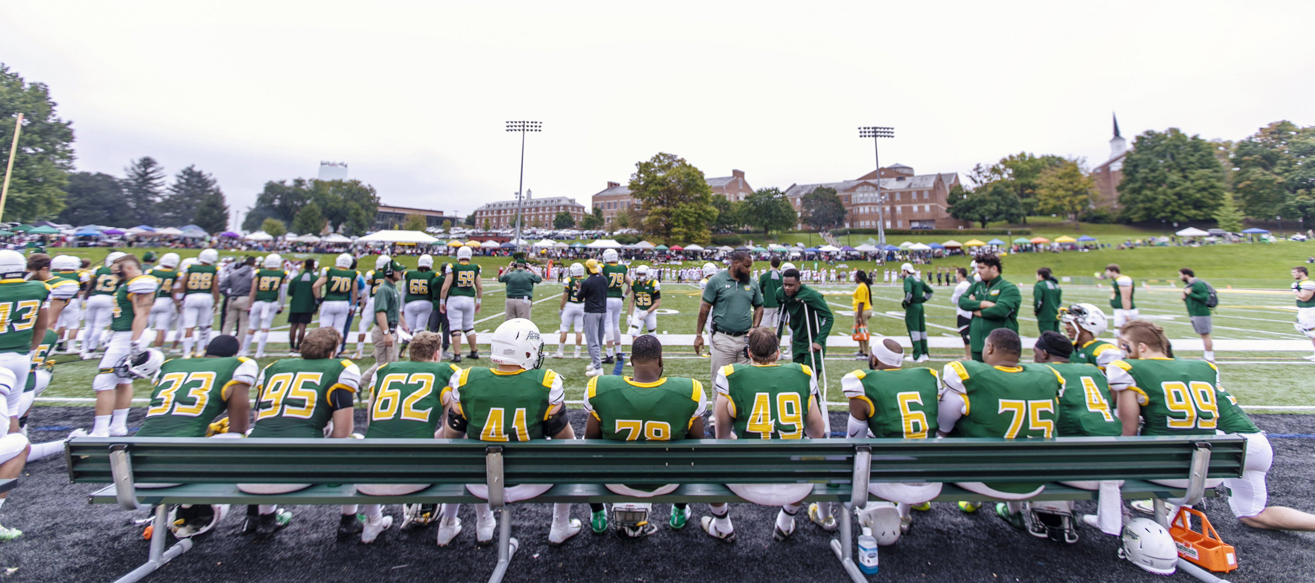 Football players sitting on the bench during football game.