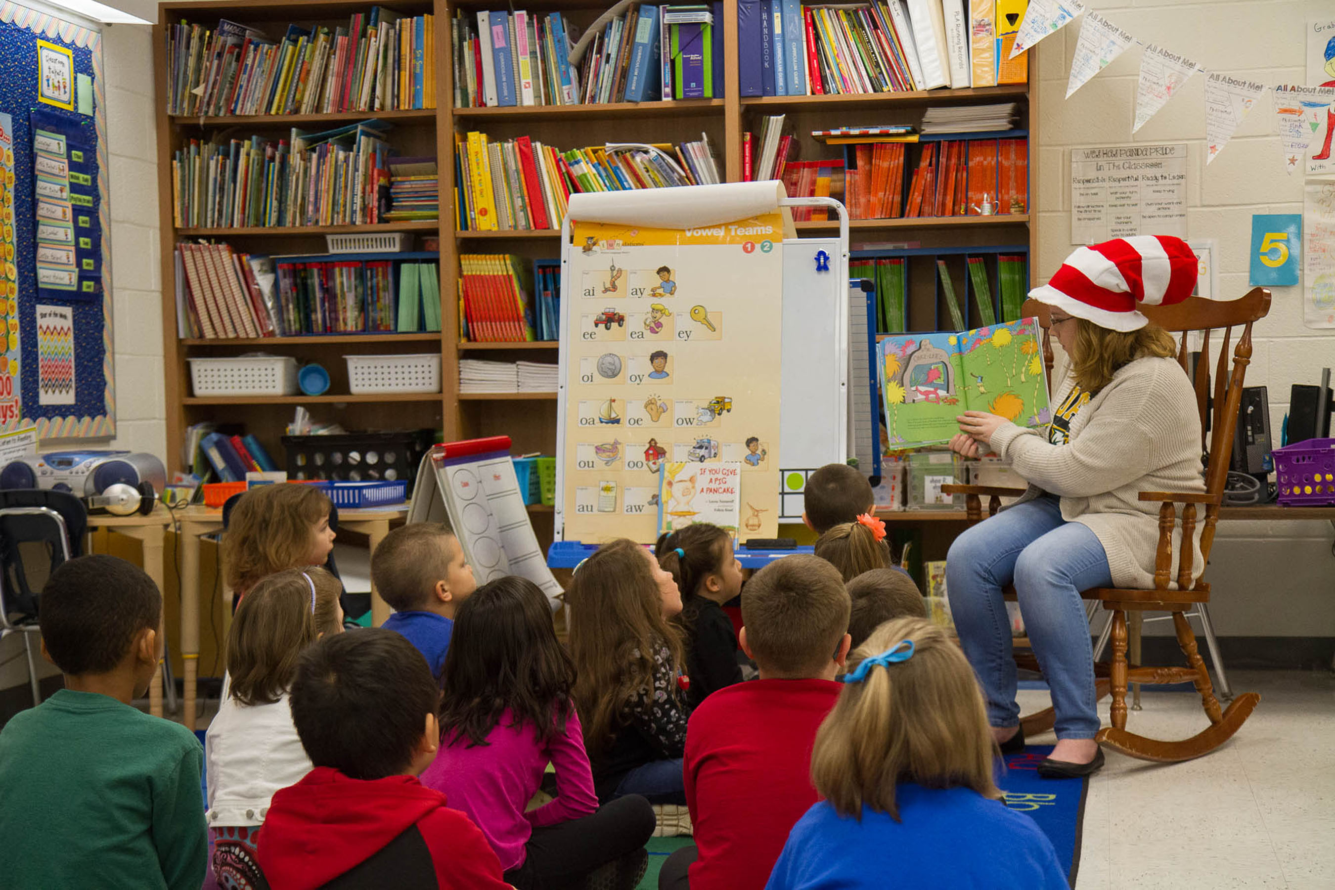 Student reading to a classroom full of elementary school children.