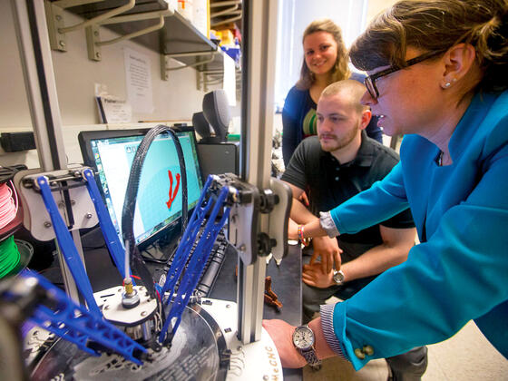 Biology professor guiding students in 3D printing.