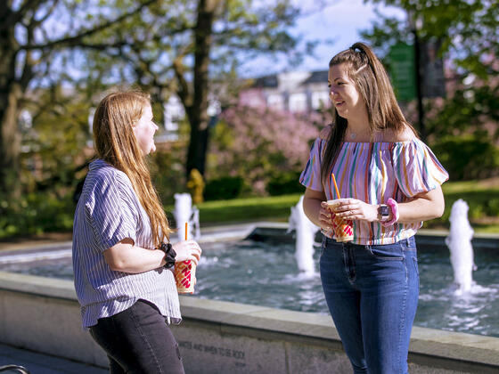 Two students in conversation near fountain on campus.