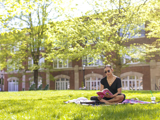 Student reading book sitting on lawn on campus.