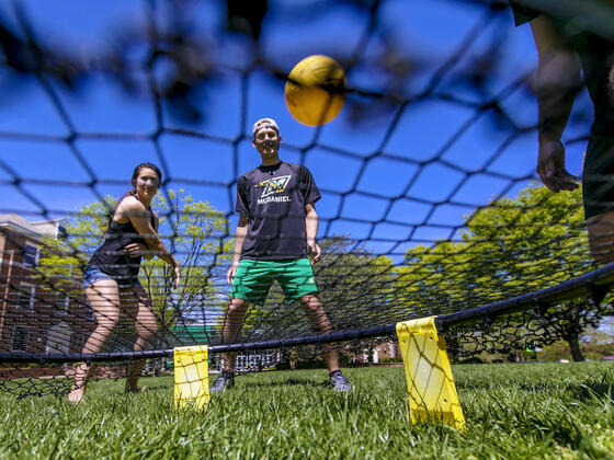 Students playing Spikeball on campus lawn.