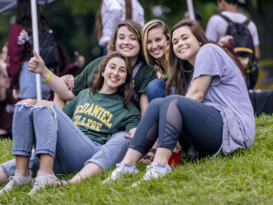Students together on lawn at Homecoming football game.