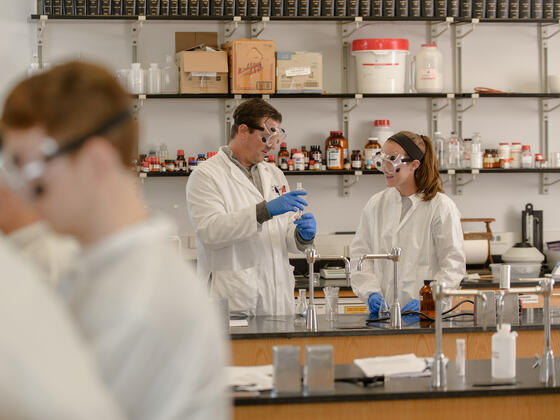 Professor with students in research lab.