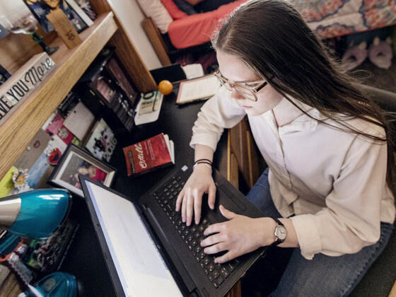 Students on computers in residence hall room.