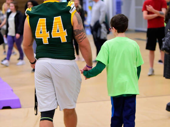 Football player holding child's hand at Tournament of Champions