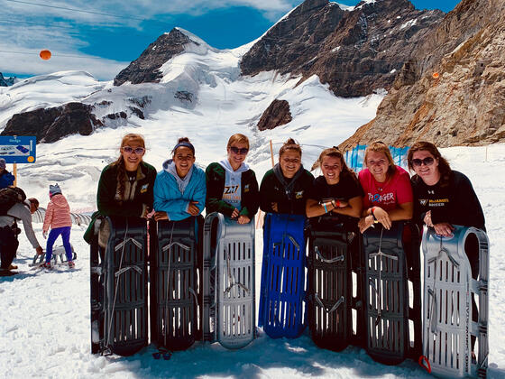 Women's Soccer team in the Alps, standing with sleds.