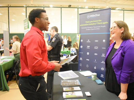 An employer talks to students at a job and internship fair.