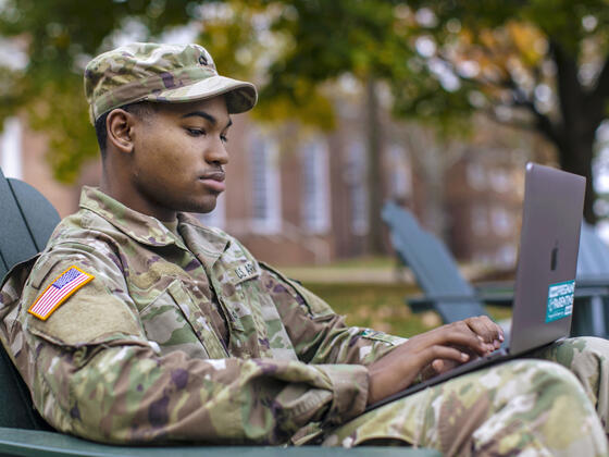 ROTC student in uniform sitting in outdoor chair on campus.