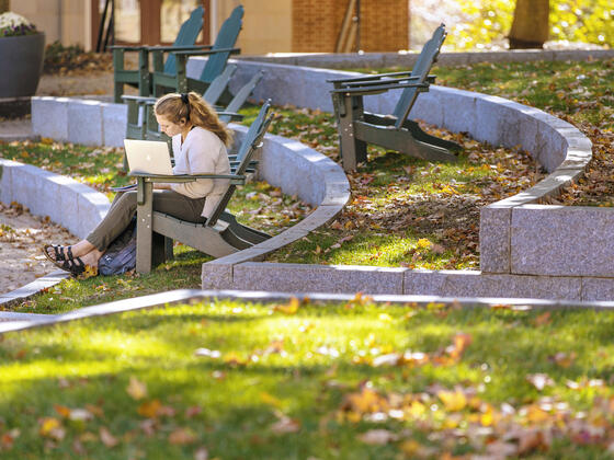 Student sitting in outdoor chair on campus.