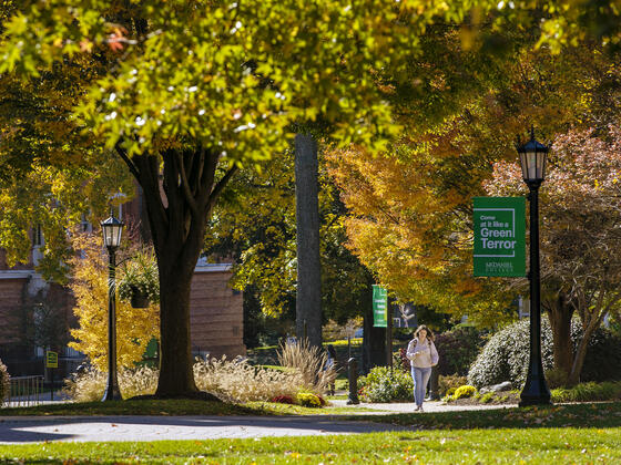 Fall campus view with student walking on sidewalk.