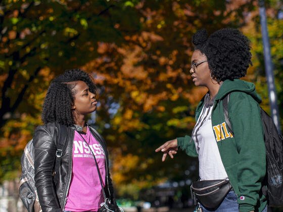Two students chatting outdoors on a beautiful fall afternoon.