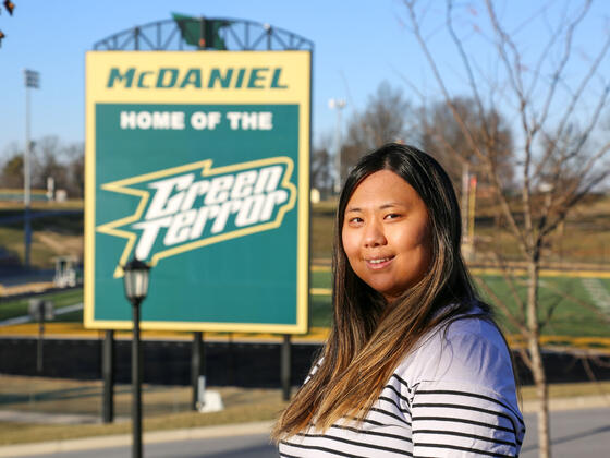 Brianna Myung standing on campus with the McDaniel Home of the Green Terror sign in the background.