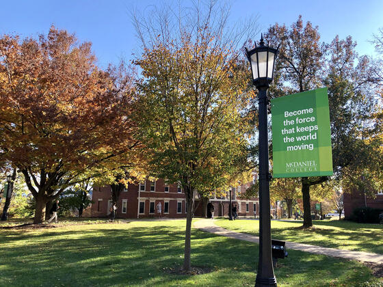 McDaniel College campus in Fall with Keep the World Moving banner