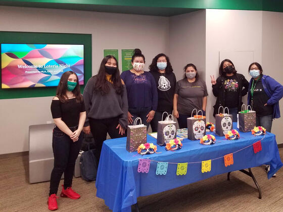 "Seven students stand in front of a table with various background. Powerpoint in the background reads ""Welcome to Loteria Night. Presented by HLA, ODEI, and OSE."""