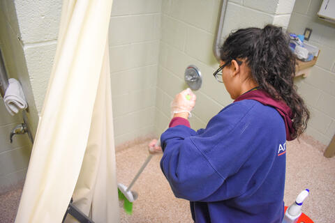 McDaniel freshman Sofia Mendez cleans the bathroom at the Cold Weather Shelter in Westminster on Monday.