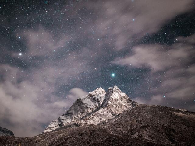 Clouds and stars over a mountain