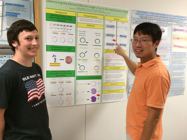 Senior Garrett Gregoire discusses his research with Biology professor Cheng Huang.