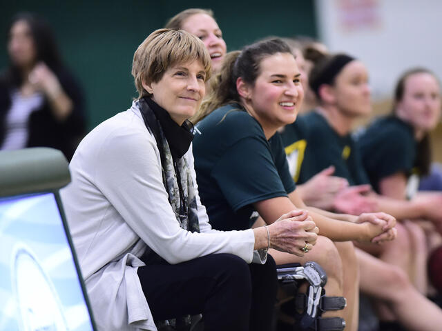 Coach Becky Martin sitting with basketball players on the sidelines.