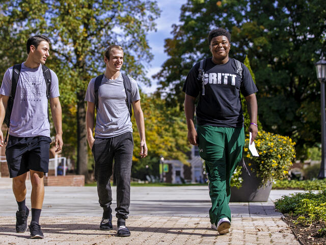 Three students walking together on campus.