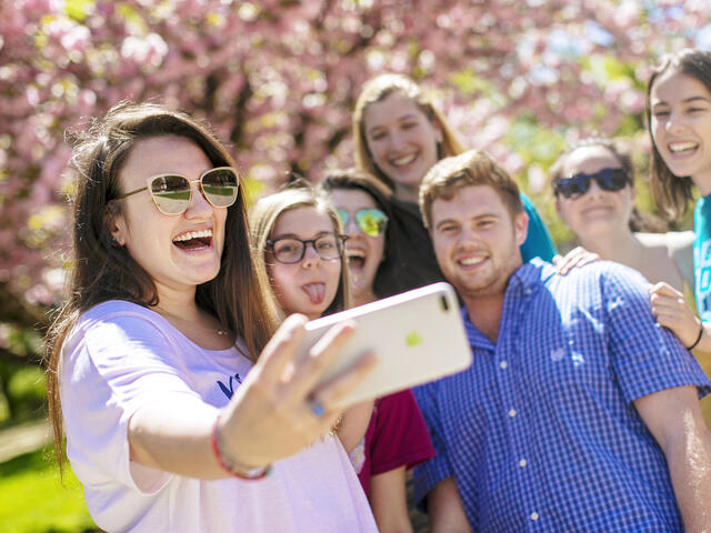 Students taking group selfie outside on campus.