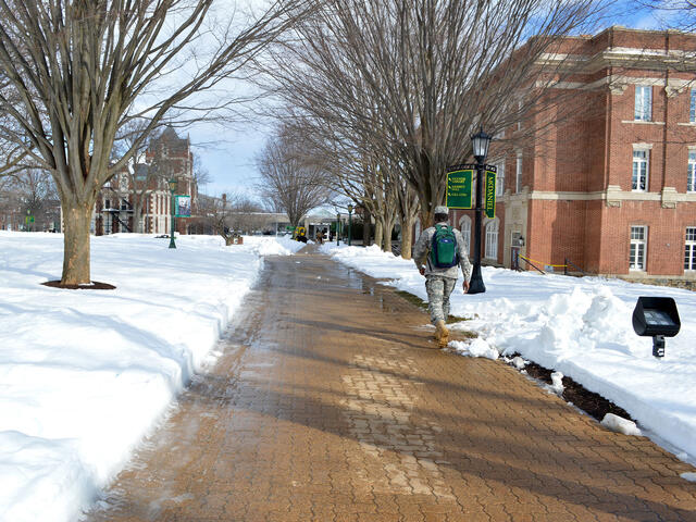Student walking across campus sidewalks in the snow.