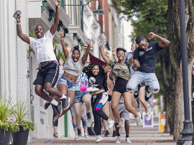 Students jumping in the air on a sidewalk in downtown Westminster.