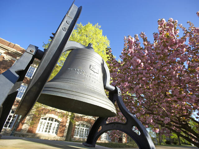 Bell in front of campus in spring