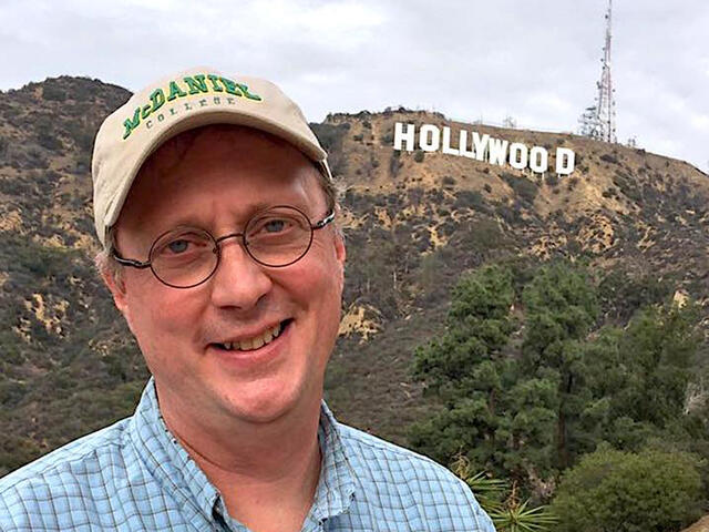 Hollywood Insider Jonathan Slade, Cinema Prof in front of Hollywood sign.