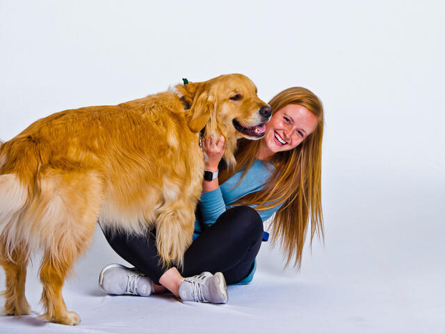 Morgan Collinson sitting with her golden retriever.