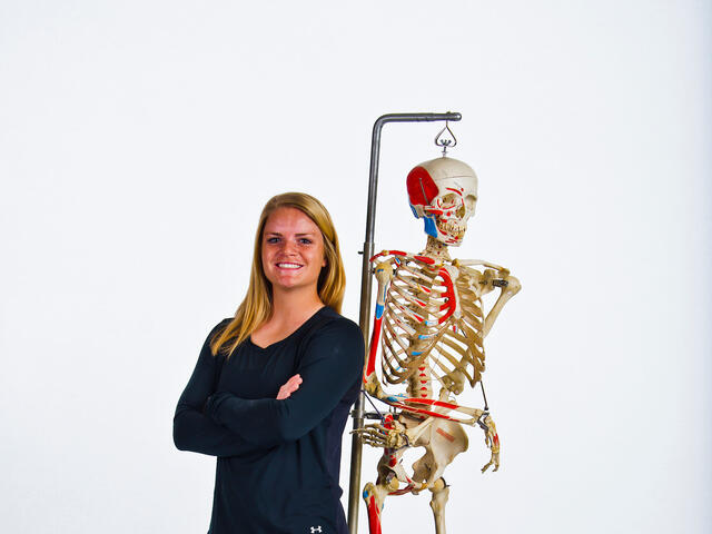 Olivia Maenner standing next to a lab skeleton.