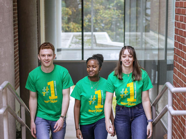 Students walking up stairs on campus wearing #1 Best Value T-shirts.