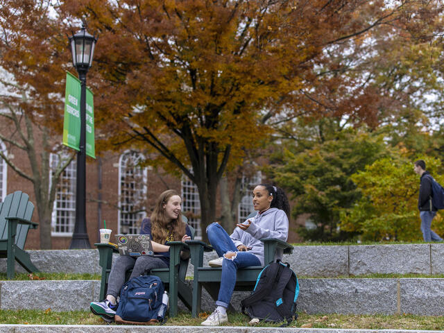 Students sitting in outdoor chairs on campus.