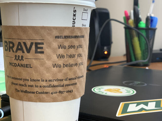 Starbucks coffee cup with BRAVE-McDaniel on paper coffee sleeve sitting on desk next to laptop.