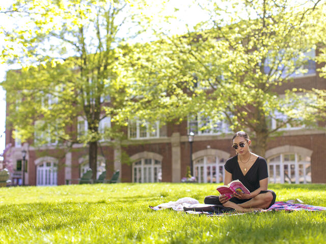 student reading a book in the grass