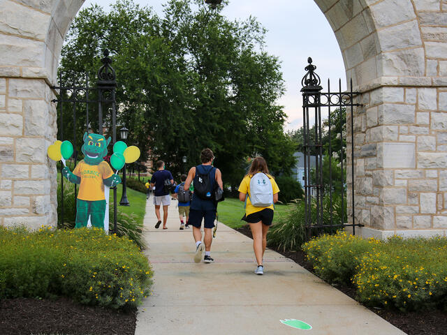 students walk under arch, past the Green Terror