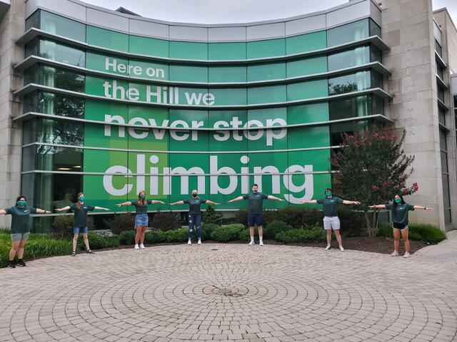 "Seven students stand six feet apart in front of McDaniel College Gill Center sign that reads ""Here on the Hill we never stop climbing""."