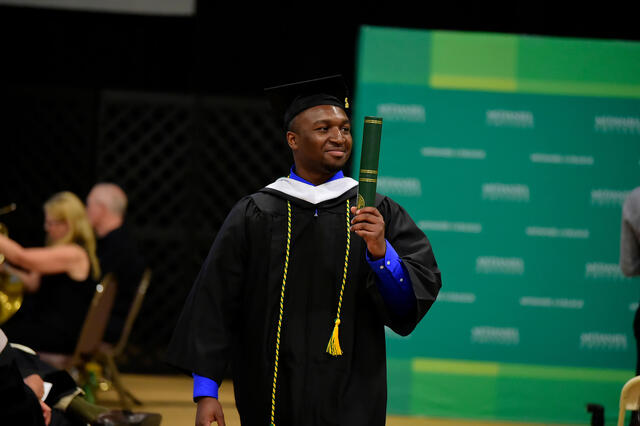 Student with diploma in hand at Commencement 2019.