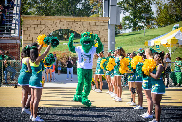 Green Terror mascot with cheerleaders.
