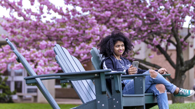 Student sitting in outdoor chair on campus listening to music.
