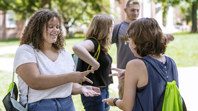 Students playing rock paper scissors on campus.