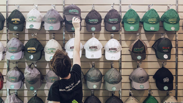 Student selecting McDaniel hat in campus bookstore.