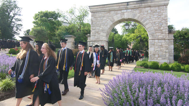 Graduates walking through the Arch at Convocation.