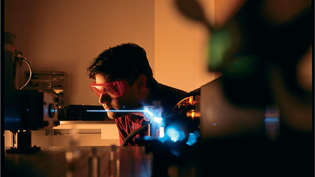 Student wearing goggles in a dark lab using lasers.