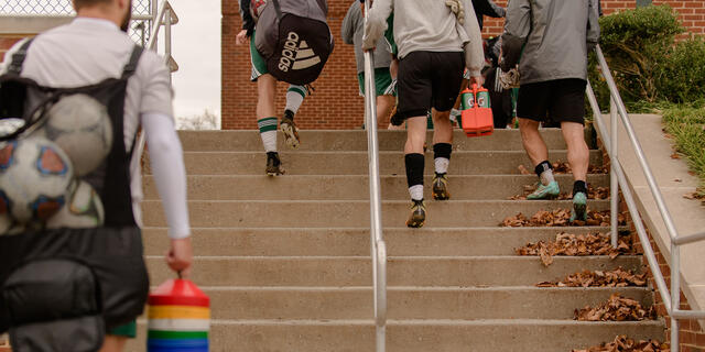 Athletes climbing staircase on campus.