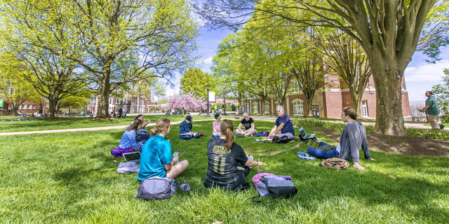 Professor lecturing class outdoors sitting on campus lawn.