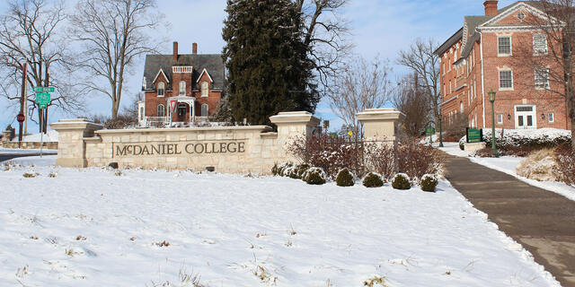 McDaniel College entrance sign in winter snow.