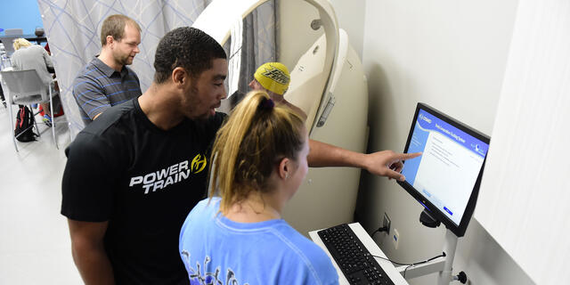 Students with professor in Kinesiology lab.
